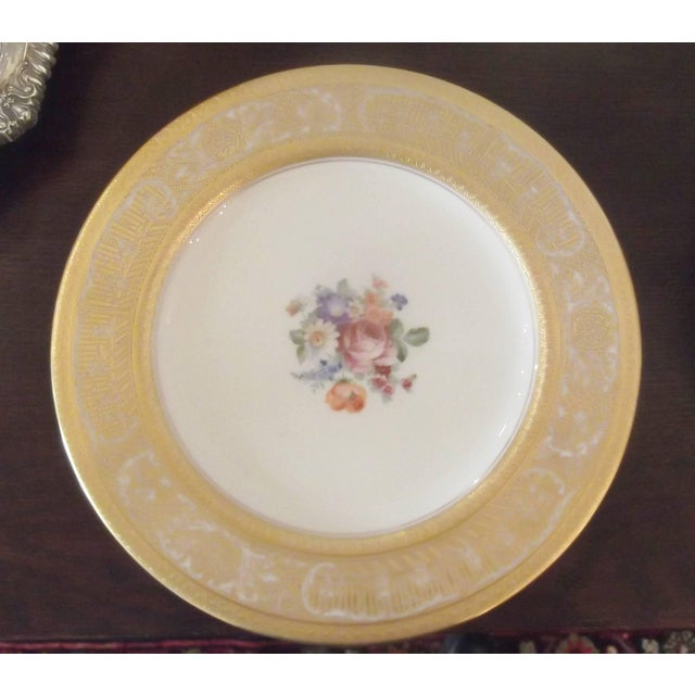 A set of 12 heavy gilt bordered service plates with floral centers. Textured gilding around the edge with delicate floral...