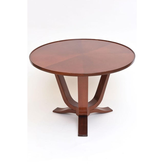 The radially veneered circular top above curved supports and legs joined by a central hexagonal support. Provenance...