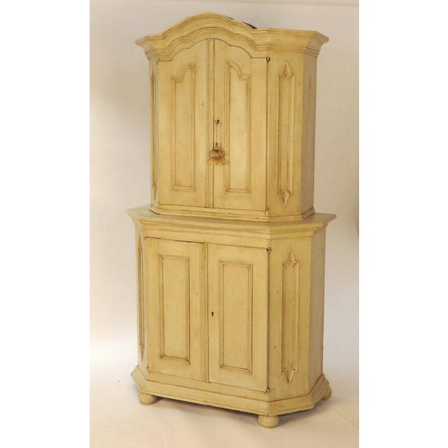 A late 18th, early 19th Century classical rustic Swedish Baroque 2 part painted cupboard. The doors have architectural...