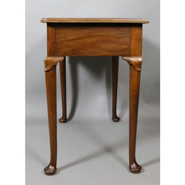 With rectangular top with molded edge over a single drawer raised on circular tapered legs headed by lambs tongue carving,...