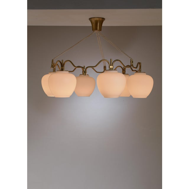 A round brass chandelier with six opaline glass shades, by Bent Karlby for Lyfa. We have a second lamp of this model...