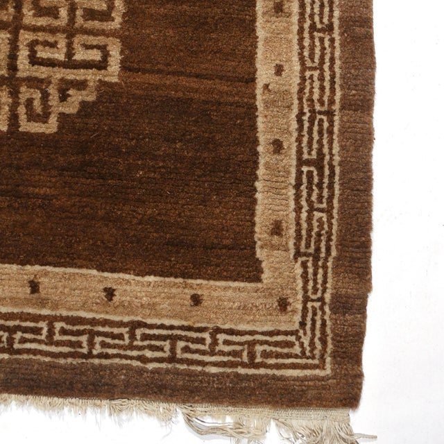 Mongolian throw rug in chocolate brown with three medallions and fringe ends.