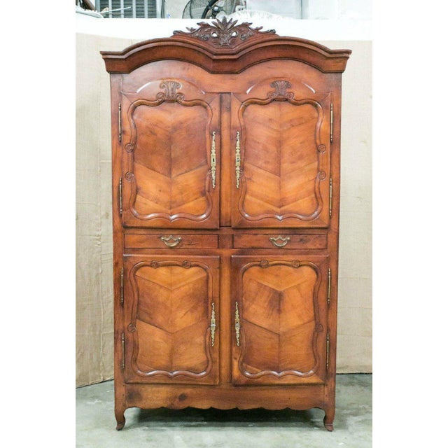 Louis XV armoire handcrafted between 1750 and 1760 in Rennes of solid wild cherrywood. Double chapeau de gendarme cornice...
