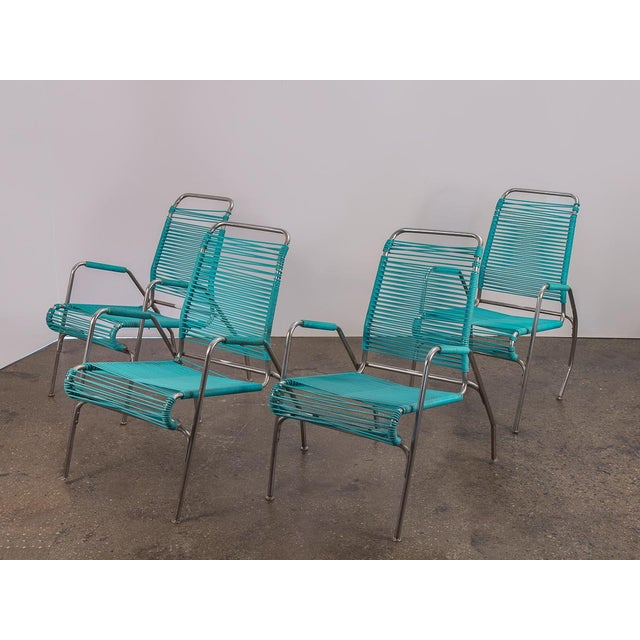 1960s Ames Aire Set of Four Patio Chairs with teal vinyl cording. Add this fun, modern set to your patio or garden for...