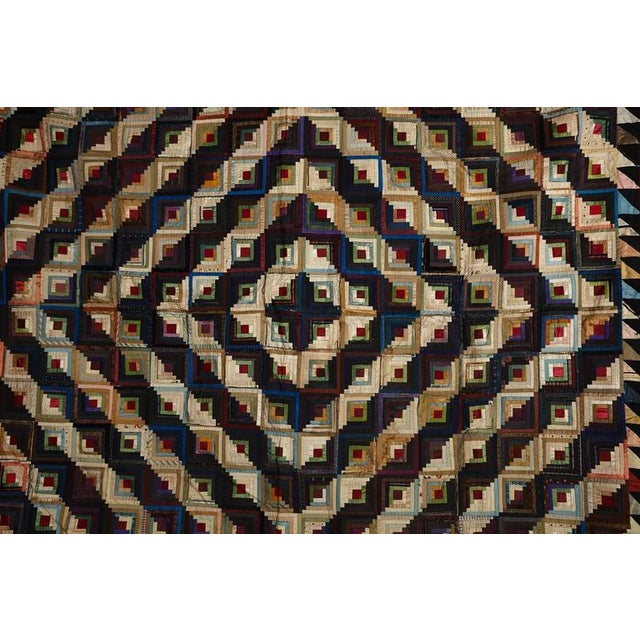 A multitude of blocks approximately 3 1/2 square are pieced of narrow 'log' strips of silk. These are arranged by light...