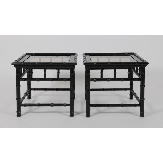 A pair of black painted faux bamboo tables with glass tops. The old glass has a slight tint, with some marks and slight...