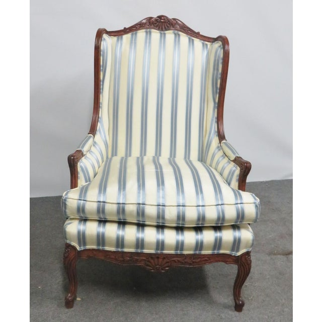 Louis XV style wing back chair, carved walnut frame, blue and white striped fabric.