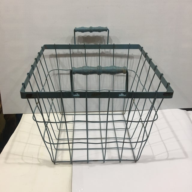 A beautiful blue wire basket with wood handles. Great decorative accessory.