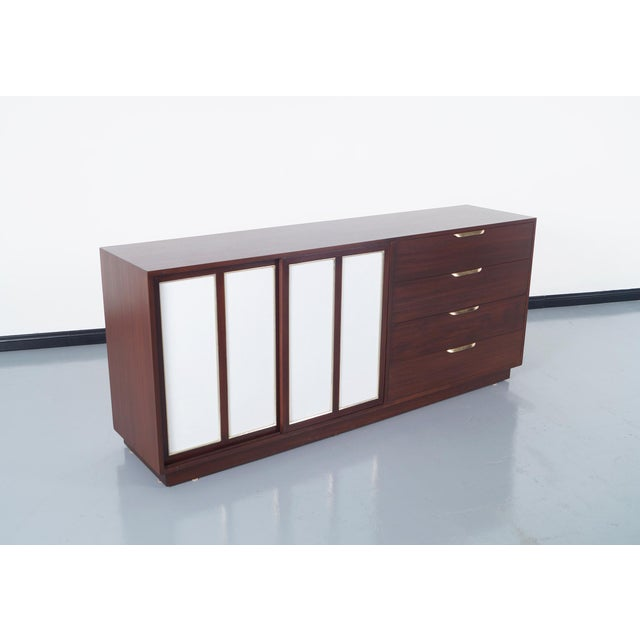 Elegant vintage sideboard designed by Harvey Probber. Features two leather sliding doors on the left revealing white...