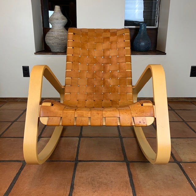 The Dondola rocker, purchased in 2004 for $2200 from Design Within Reach, is made of laminated ash with tan leather...