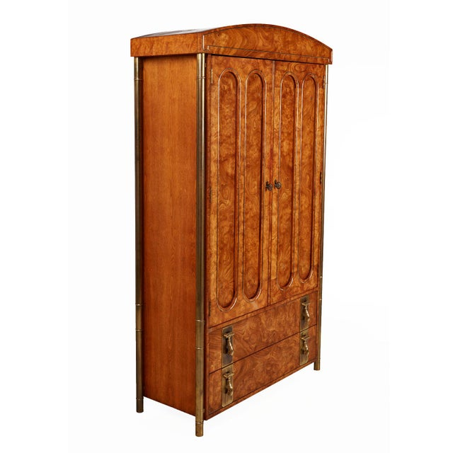 Breathtaking burl wood and brass Mastercraft armoire. Four tubular outer skeletal brass support legs create a floating...