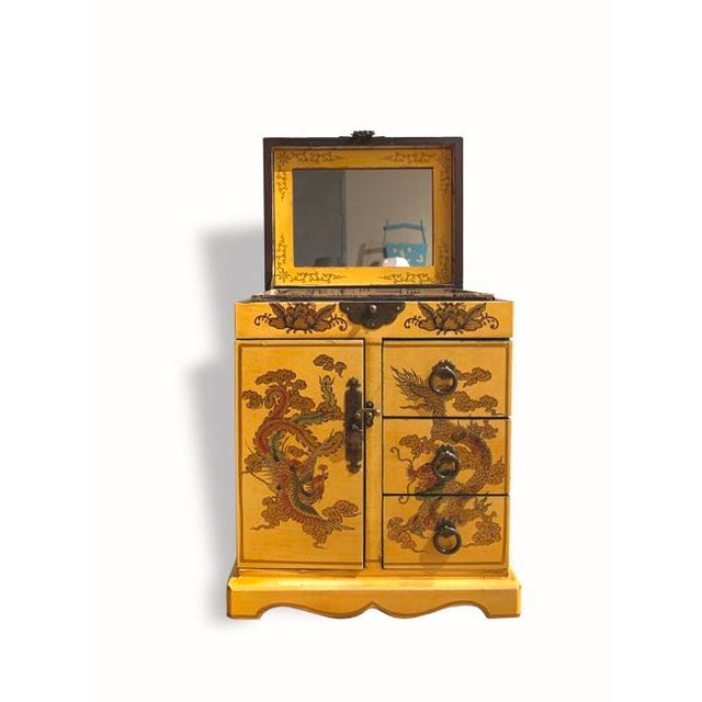 Wooden Yellow Asian jewelry box with gold dragon detailing. Includes a mirror that flips up on the top, three drawers, and...