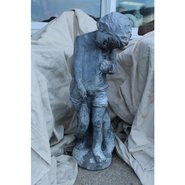Cast lead 1920s classic garden statue of a boy holding a fish. Made of very sturdy and heavy cast lead with weathered...