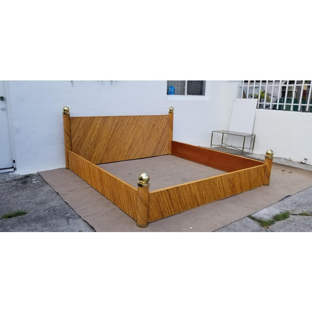 Impressive Cannon brass ball and a bamboo king-size bed. Head & Footboards in angled rattan bands. Overscaled gold tone...