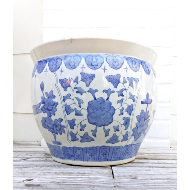 Large blue and white pot featuring a floral and bird motif. Greek key design around the rim.