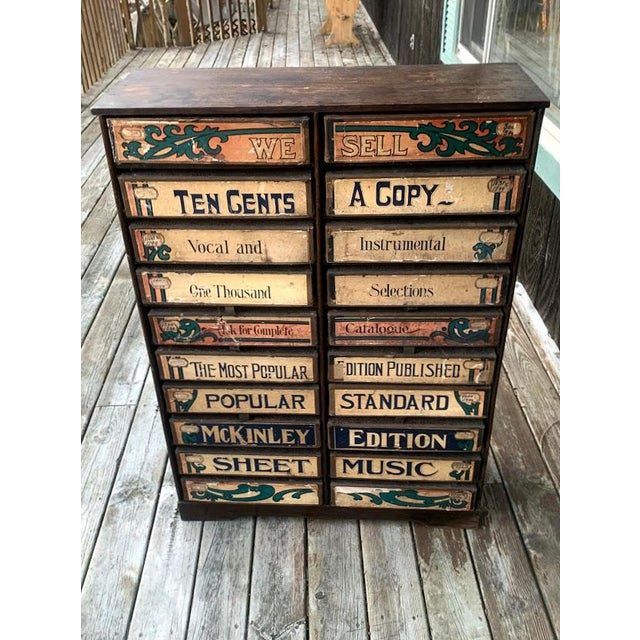 This 1920s era wooden cabinet was used to house sheet music in a retail setting. There are 20 pullout cardboard drawer...
