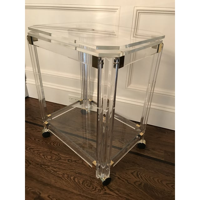 Glamorous Vintage Lucite two-tiered rolling bar cart or TV table. This cart sits on brass capped casters which roll...