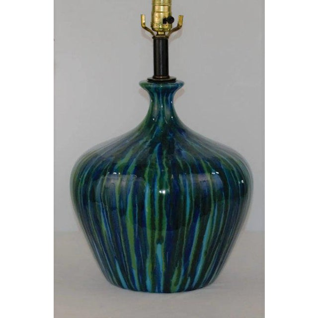 A fantastic table lamp featuring a deep blue green glaze. The incredible combination of the blue and green glaze flows...