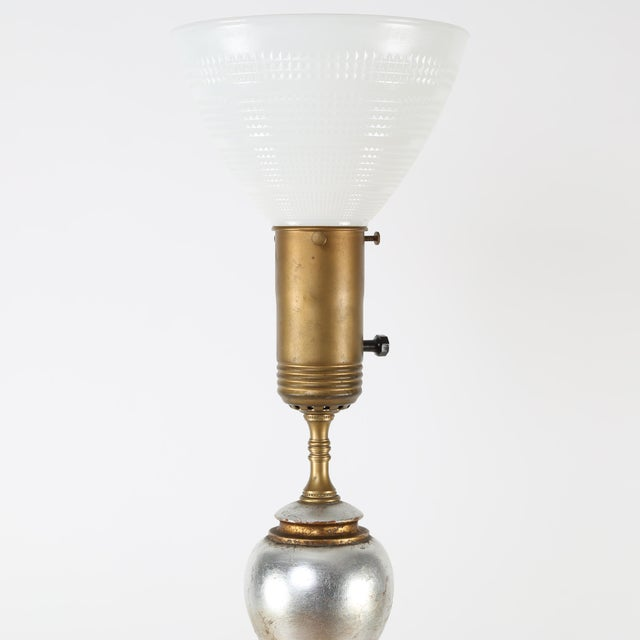 This striking and large table lamp features four stacked and graduated balls finished in gold and silver leaf. 3-way mogul...