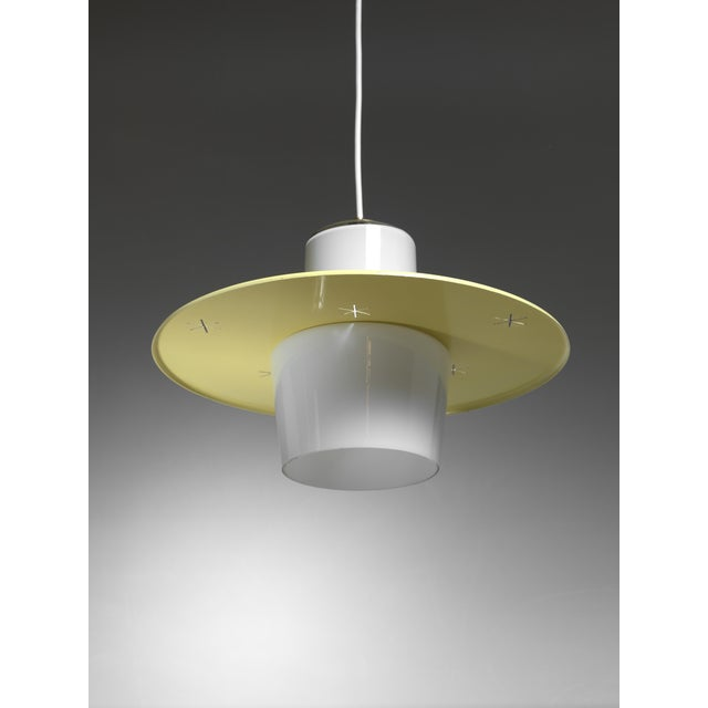 A model K2-23 pendant by Paavo Tynell. The lamp is made of a opaline glass diffuser with a round yellow metal shade with...