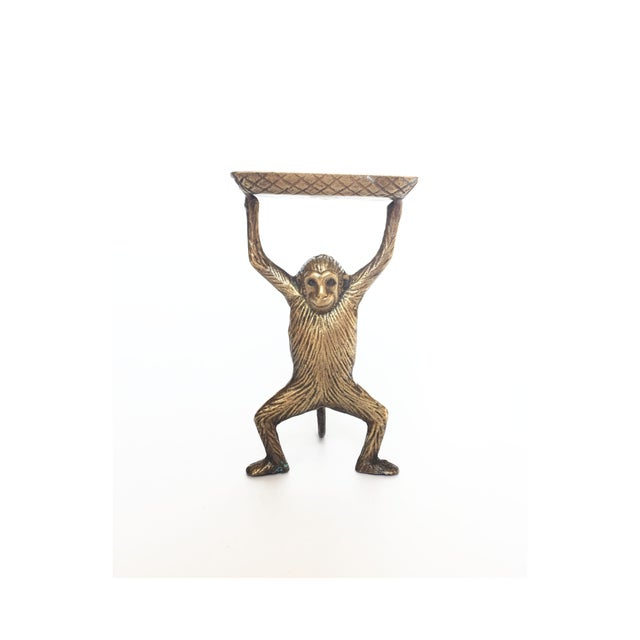 A wonderful monkey raising a dish over its head formed in heavy gold brass. The perfect size to hold business cards or a...