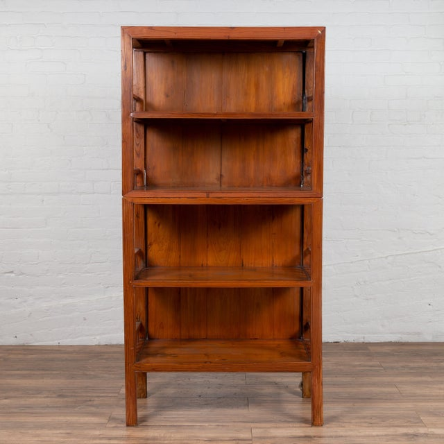A vintage Chinese two-part elmwood bookcase from the mid-20th century, with pillar-shaped strut motifs and four shelves....