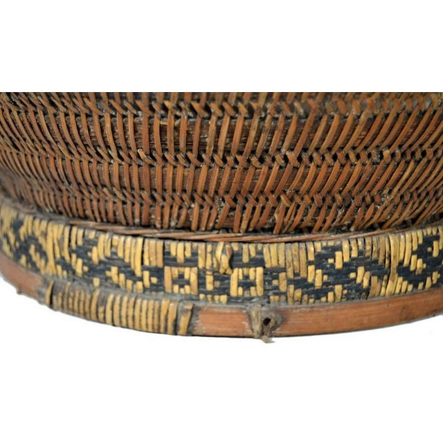 A 19th century Chinese grain basket handwoven of cane and bamboo. In 19th century China baskets such as these were used to...