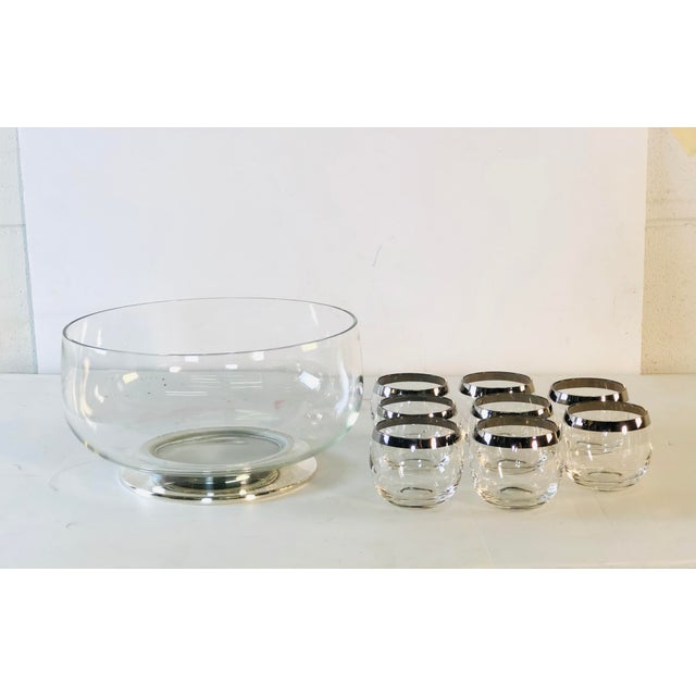 1960s glass punch bowl set with 8 silver rim roly poly style tumblers. The punch bowl has a silver plated base and the...