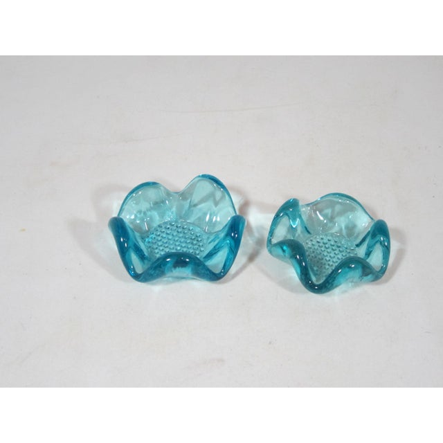 """Set of two Mid-Century flower shaped nut dishes made of turquoise glass. The dimensions are 3 3/4"""" W x 3 3/4""""D x 1 1/2""""..."""