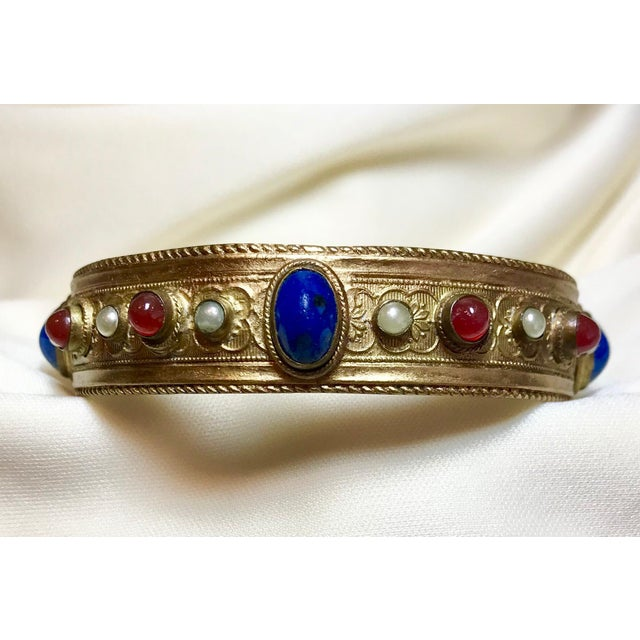 Circa 1920s plated brass bangle with a raised floral design and a rope motif edging. It is bezel set with glass cabochons...