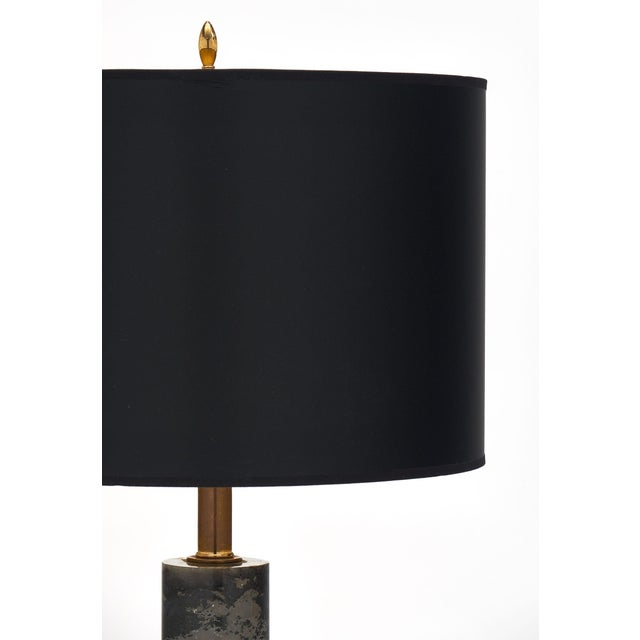 French Modernist marble table lamps with a Turquin marble cylinder supported by an ebonized wooden base. The brass...