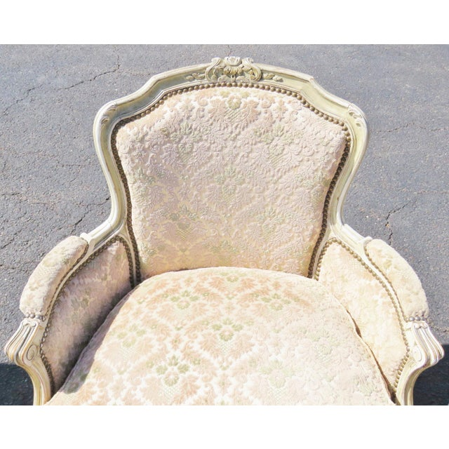 Louis XVI style bergere chairs with distressed cream panted and carved frames. There is wear to paint on frame
