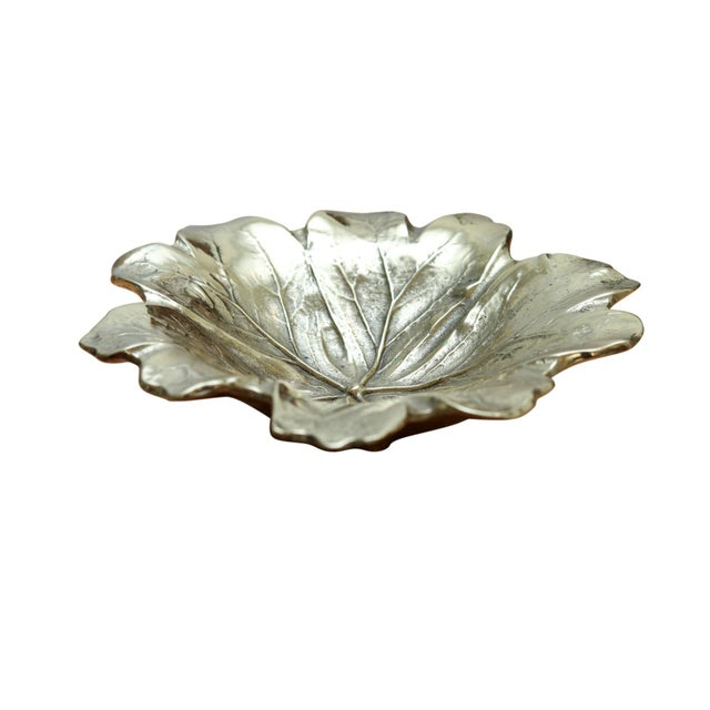 "A cast brass dish shaped like a Mayapple leaf. Made by Virginia Metalcrafters, reads ""Copyright 1948 Mayapple 4 - 6""..."