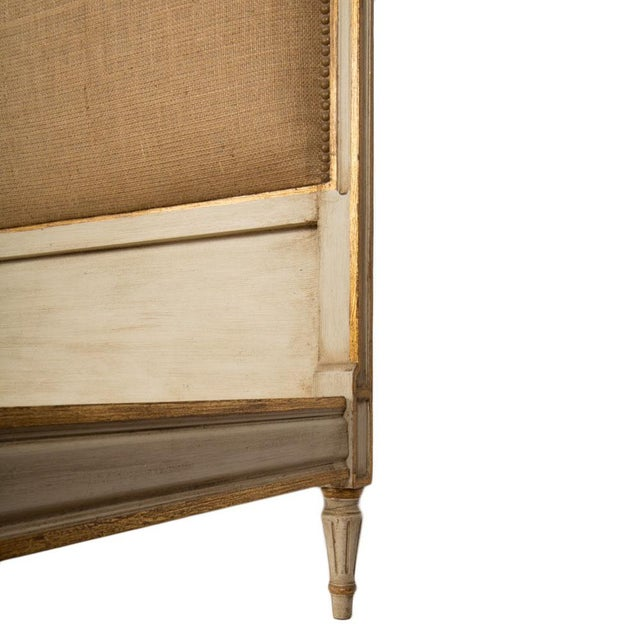 """A French Louis XVI style painted and gilt burlap upholstered bed circa 1940. Interior: 76"""" x 59"""" Foot board: 28""""Tall This..."""