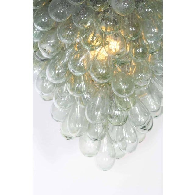 A modern light fixture, featuring blown glass styled as a grape cluster, suspended from circular flush mount canopy....
