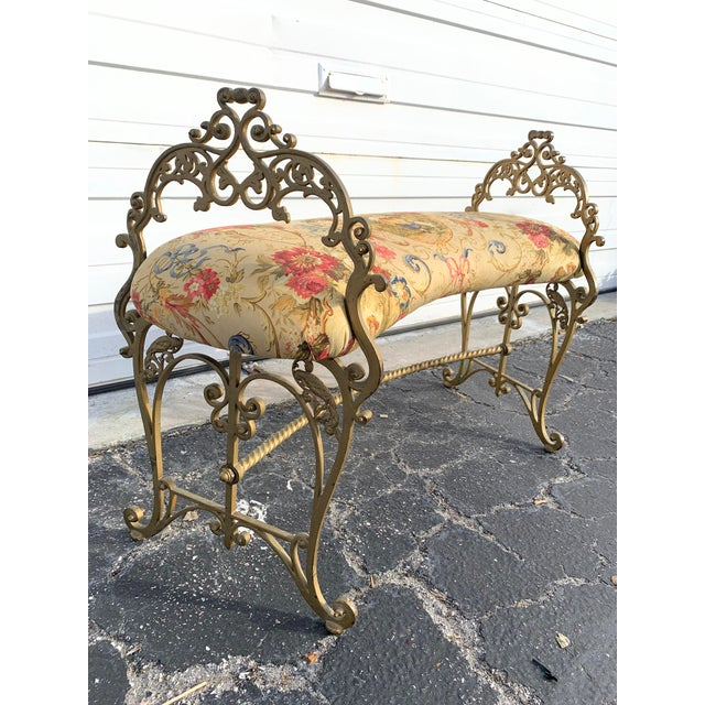 Gilt French vanity bench or boudoir bench. Frame is made of swirly gold gilt designs and parrot accents on side. Kidney...
