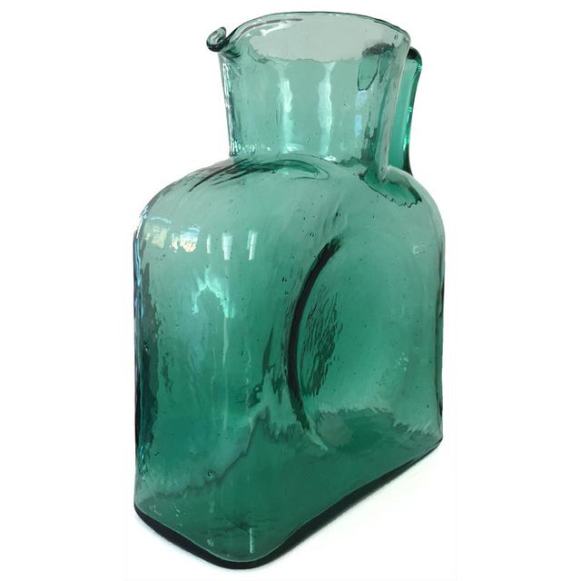 This turquoise Blenko glass pitcher is equipped with a slender handle, adding functionality as well as asymmetrical flair....