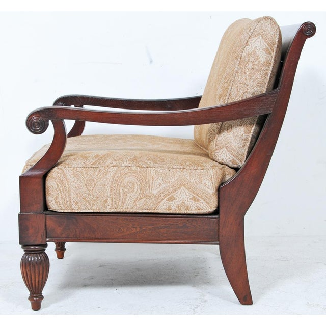 A vintage pair of large scaled carved wood armchairs upholstered in fabric that would be suitable in a covered porch...