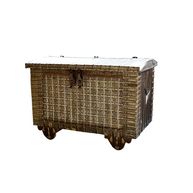 A beautifully aged 19th-Century Indian hardwood trunk on wheels that is meticulously decorated with brass and iron stud...