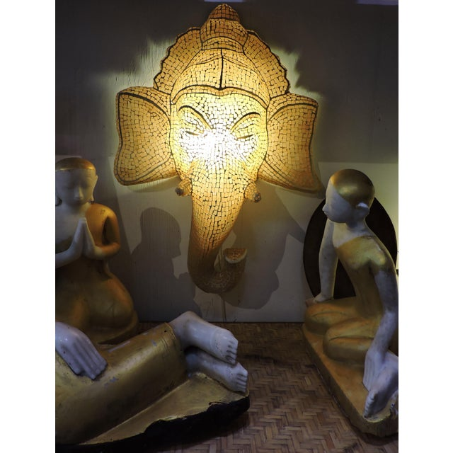 Unique wall hanging of mosaic glass Ganesh lamp. This piece glows with yellow-orange light.
