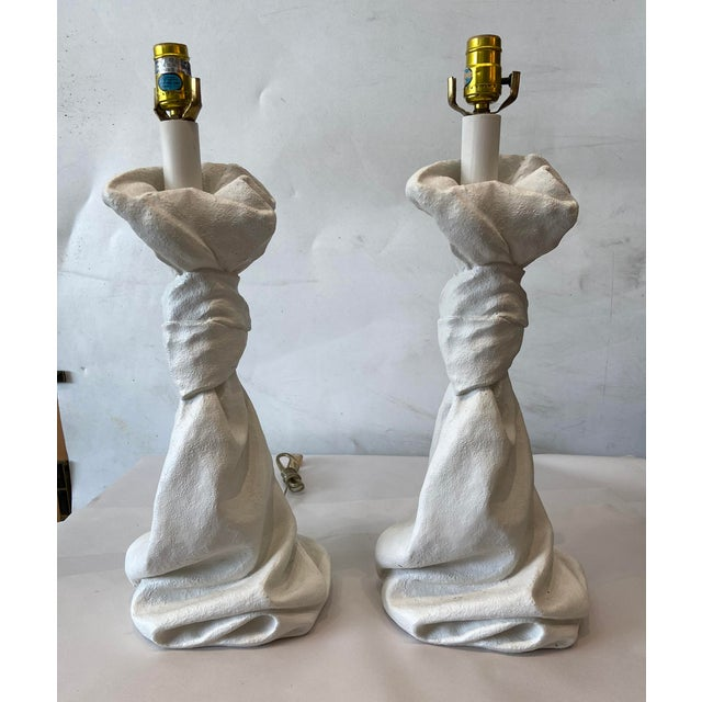 Pair of Jonathan Dickinson style plaster table lamps. Knot at the top twisted stem with a linen fold base.
