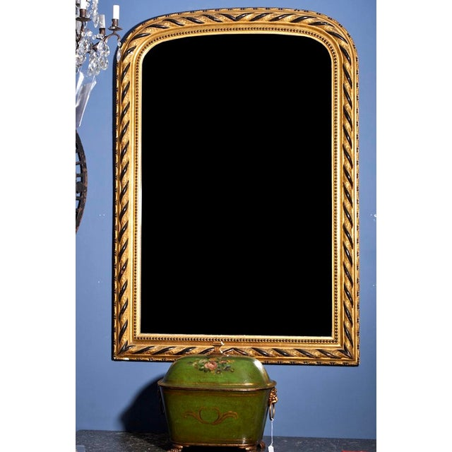 This late 19th century Louis Philippe style mirror features an elaborate gilt and ebonised frame. Original mercury mirror....