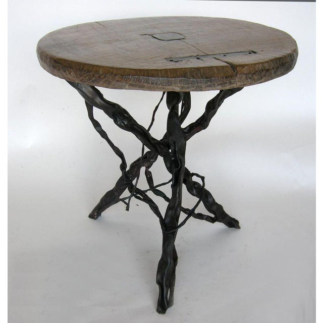 19th Century wooden wheel atop hand forged iron base. Table top repaired with iron inserts.