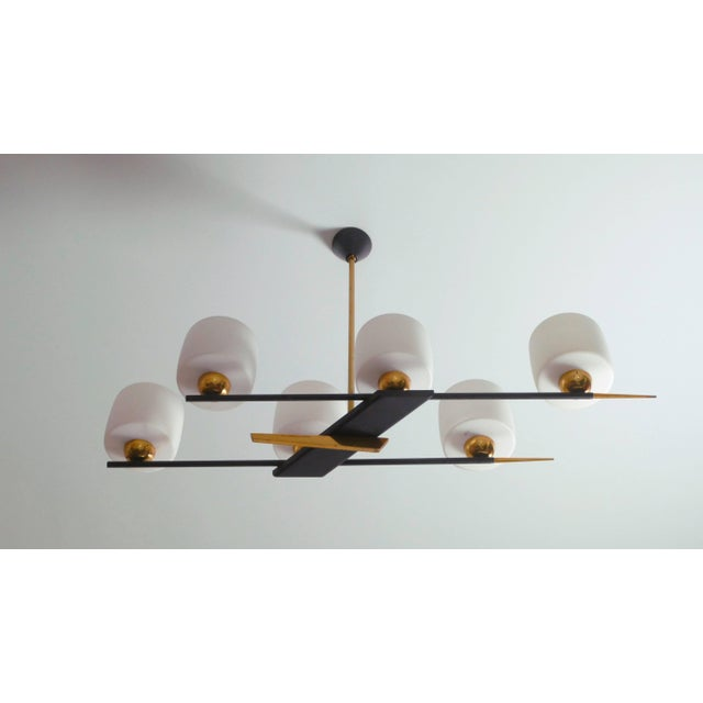 This imaginatively designed chandelier is typical of longstanding French lighting company Arlus. Contrasting black metal...