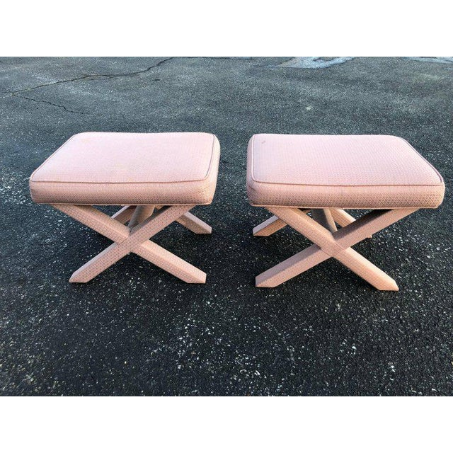 Pair of X-base stools or ottomans in the style of Billy Baldwin. Pale pinkish mauve upholstery. Could use a recover. Some...