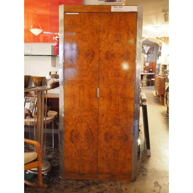 Leon Rosen burl wood bar/armoire. The doors are matchbook burl wood with great five chrome step sides. Inside has a lit...