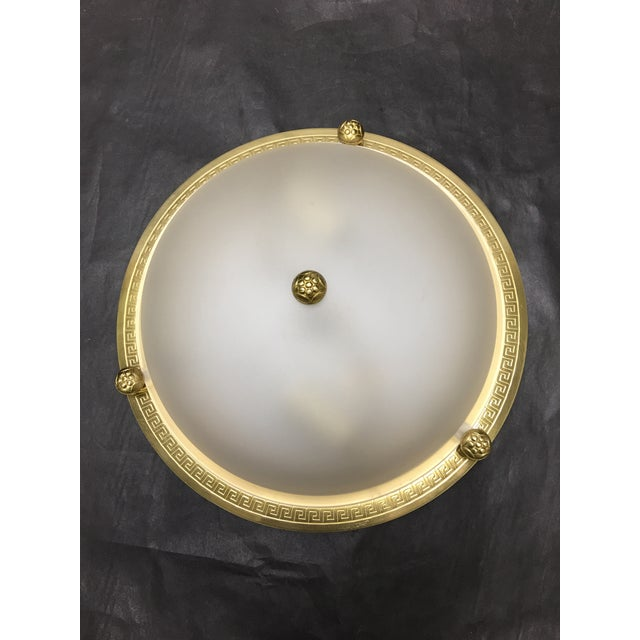 This Vaughan Regency style brass flush mount ceiling light with a Greek Key pattern and plain frosted glass globe is from...