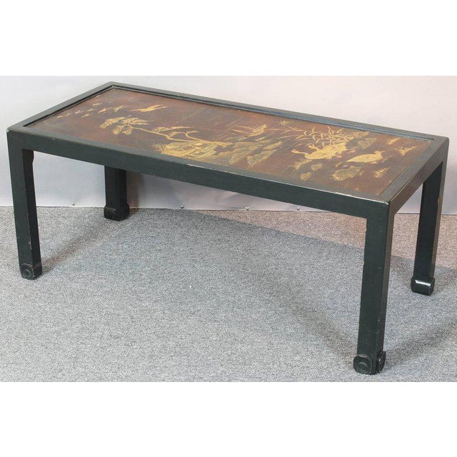 A vintage chinoiserie cocktail table with black lacquered base inset with Chinese double sided screen panel that easily...