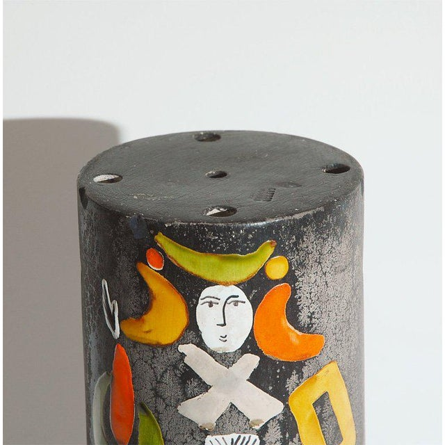 This charmingly hand-painted ceramic cylinder is a shade for a pendant lamp.