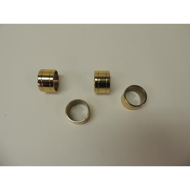 Set of 4 solid brass Ralph Lauren ribbon napkin holders. Size: 1 1/2 D x 1 D.